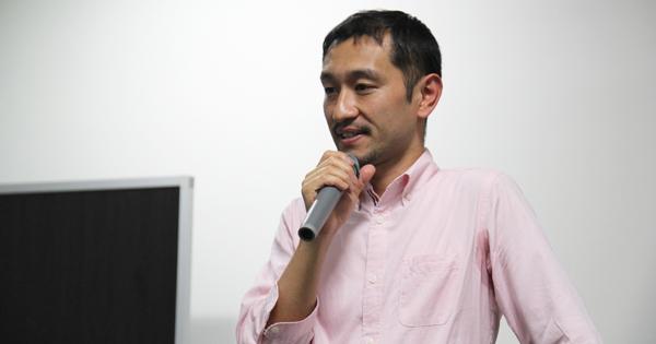 マイクを手に話している細野氏の画像
